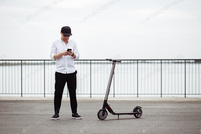 Modern man in stylish outfit using his smartphone while standing at street with electric scooter