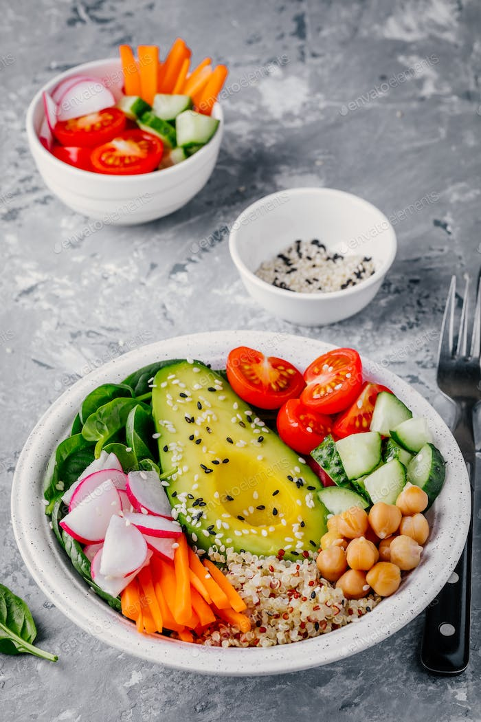 buddha bowl with quinoa, spinach, avocado, cucumbers, tomatoes, carrots, radishes, chickpeas