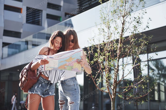 Two female tourist with map visiting a new city and is looking for a way to the hotel