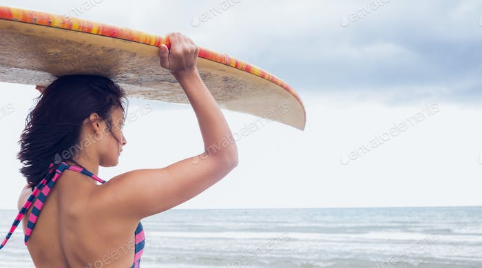 Side view of a young woman carrying surfboard on head at beach
