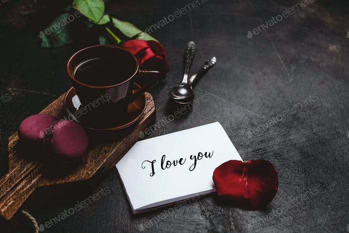 red rose, macarons and cup of coffee on wooden board with I love you greeting valentine card
