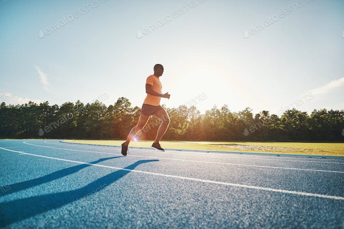 Lone athlete running along a track on a sunny day