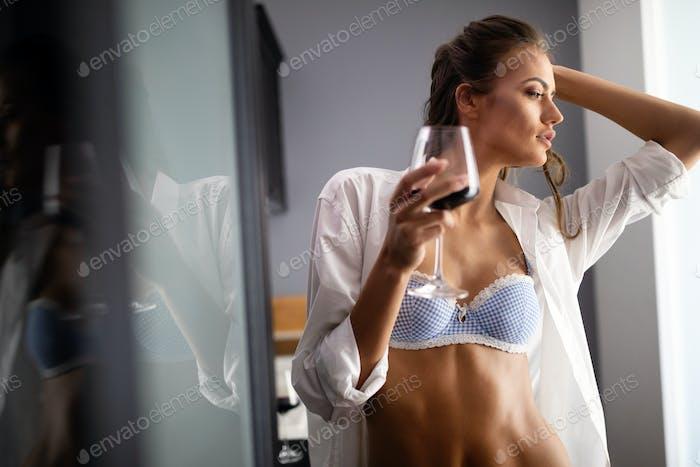 Sexy Brünette weiblich in weiß männlich Hemd über Dessous halten Rotwein in ein Glas