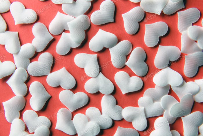 White textile hearts on red paper