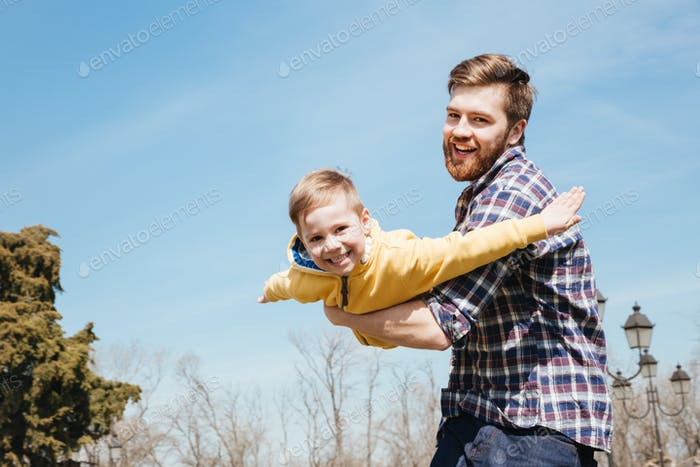 Cheerful bearded father having fun with his little son