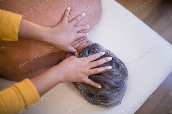 Rear view of shirtless senior male patient lying on bed receiving neck massage from female therapist
