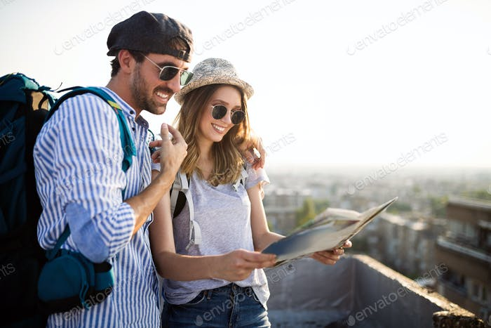Happy couple on vacation sightseeing city with map