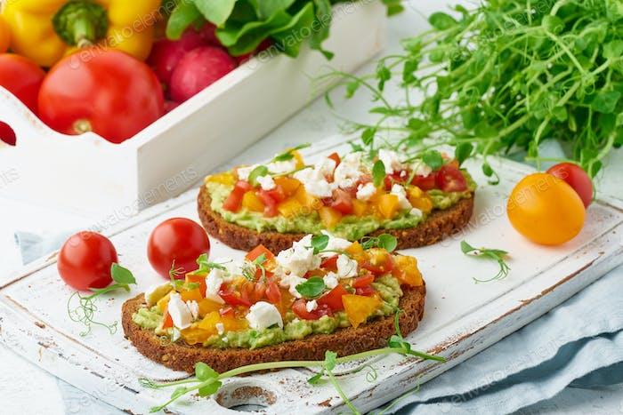 Avocado-Toast mit Feta und Tomaten, smorrebrod mit Ricotta, Nahaufnahme