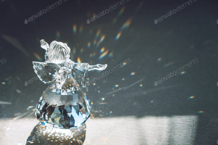 Crystal glass angel in the rays of the sun with reflecting, embossed sparkle. Faith, hope, mercy
