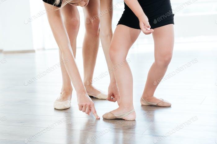 Ballet instructor directing little cute ballerina during dance practice