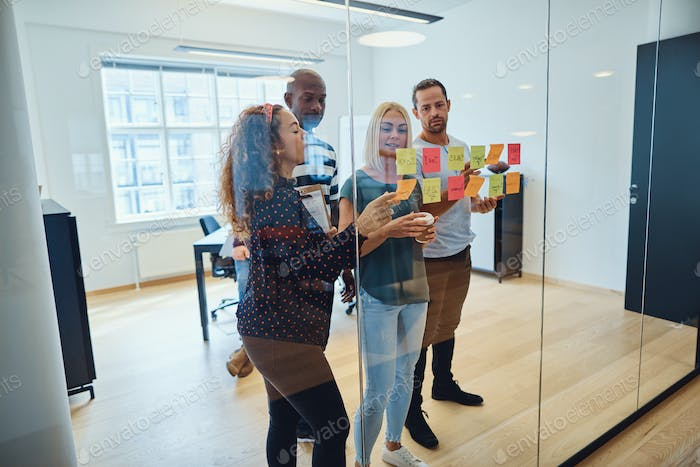 Diverse design team brainstorming with sticky notes in an office