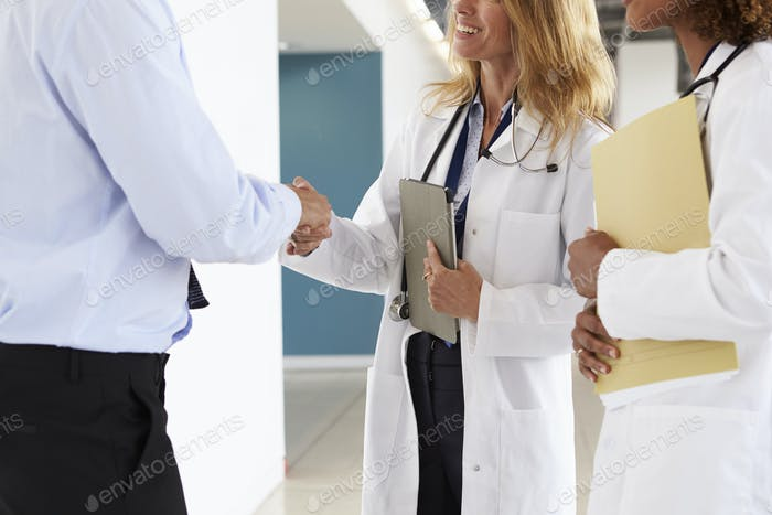 Three male and female doctors shaking hands, mid section