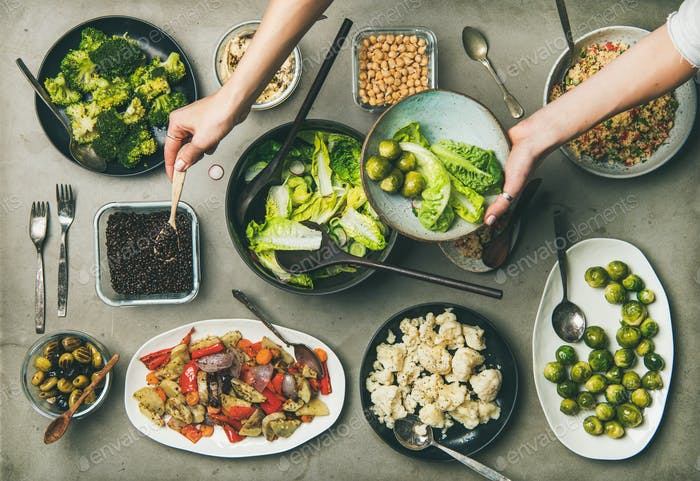 Healthy vegan dishes and woman hands mixing ingredients on plate