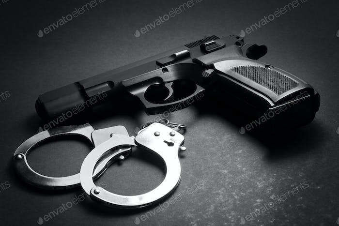 Handfeuerwaffe mit Handschellen