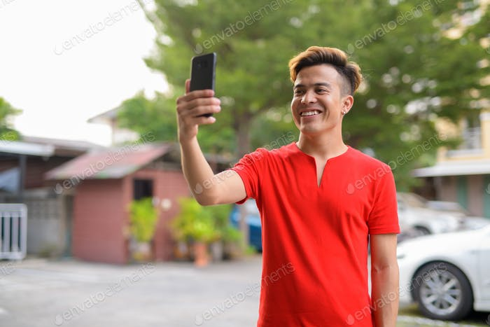 Happy young Asian man taking selfie outdoors