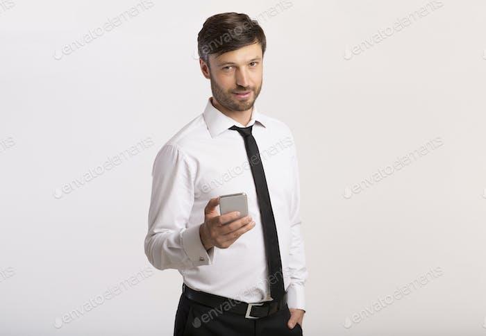 Mann hält Handy stehend auf weißem Hintergrund