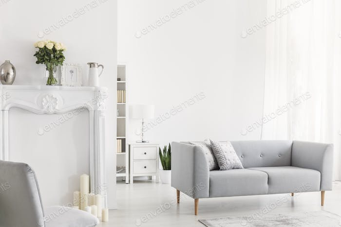 Pillows on grey settee and chair in bright white living room int