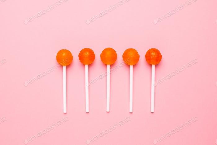 Sweet orange candy lolipop on pastel pink background. Minimalist composition.