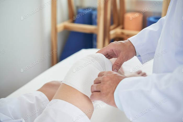 Unrecognizable doctor wrapping bandage around knee of patient
