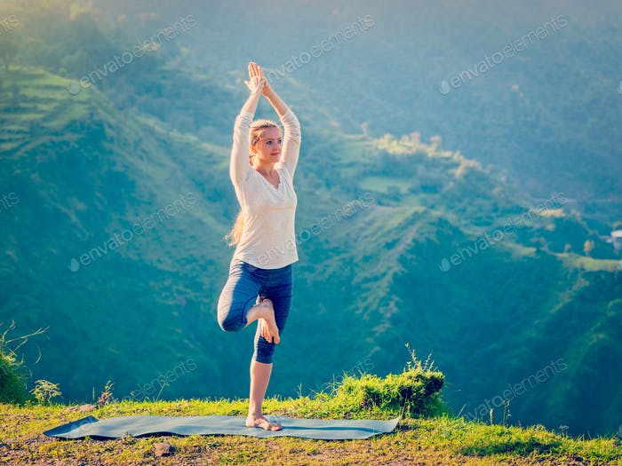 Woman doing yoga asana Vrikshasana tree pose in mountains outdoors