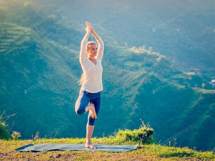 Frau tun Yoga Asana Vrikshasana Baum Pose in Bergen im Freien