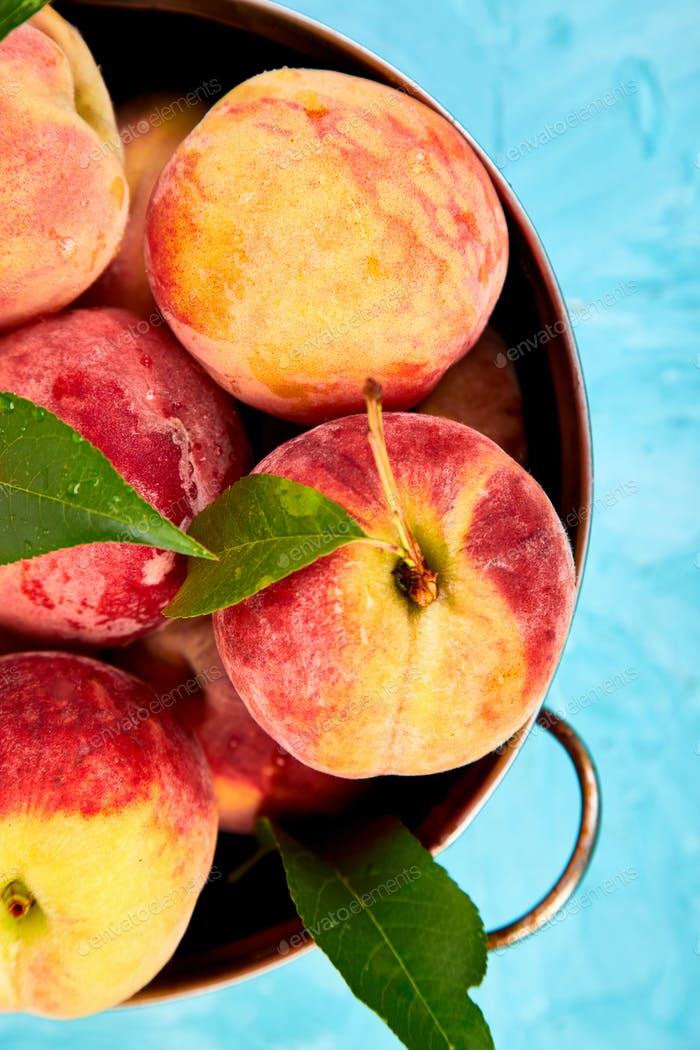 Ripe peaches in a bowl, basket on the blue table.