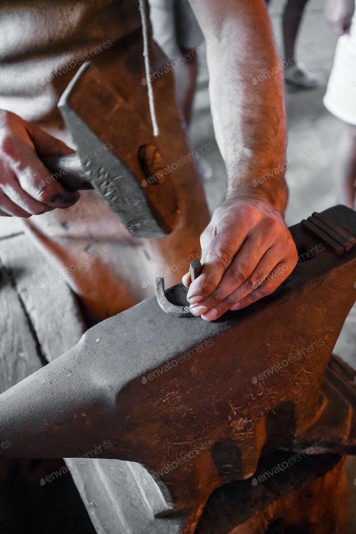 The blacksmith forging glowing horseshoe