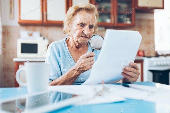 Elderly woman looking at her utility bills