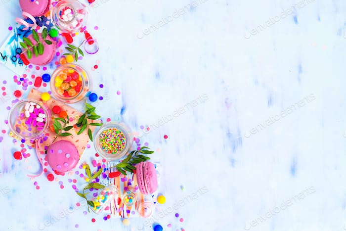 Colorful celebration flat lay with party supplies, confetti and sweets. Pink macarons in an