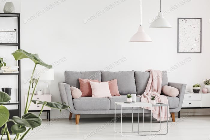 Pink cushions on grey settee in white living room interior with