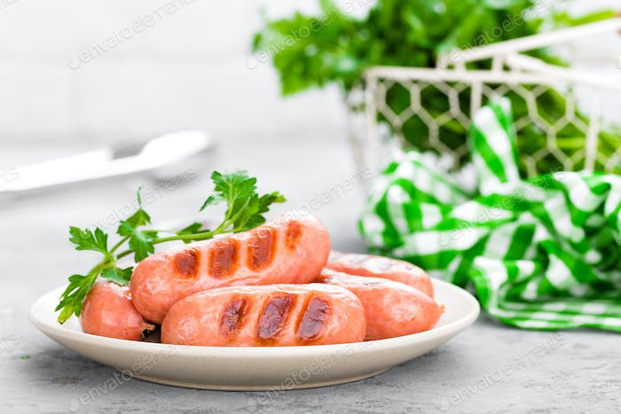 Grilled sausages on plate. BBQ sausages.