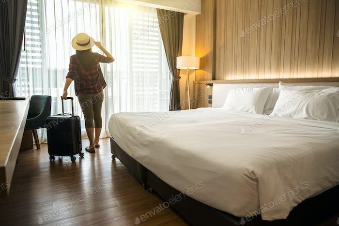 Happiness Asiatische Reisende Frau steht mit Gepäck im Schlafzimmer eines Hotels oder einer Herberge auf Reisen