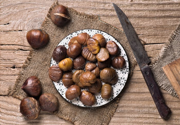 aerial shot of dish full of roasted and peeled chestnuts on rustic wood