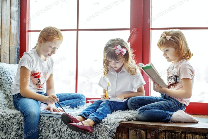 Three children read, draw and write. A group of children is stud