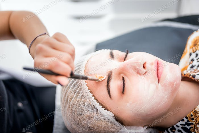 Beautician applying facial mask at beauty salon, cosmetology treatment skincare face