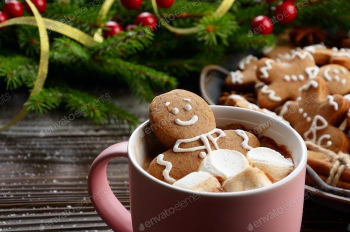 Pink mug with hot chocolate marshmallows and gingerbread man