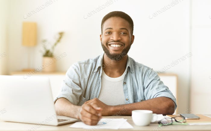 Happy african american freelancer sitting at workplace in home office