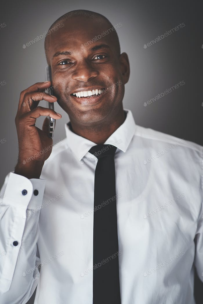 African businessman talking on his cellphone against a gray background