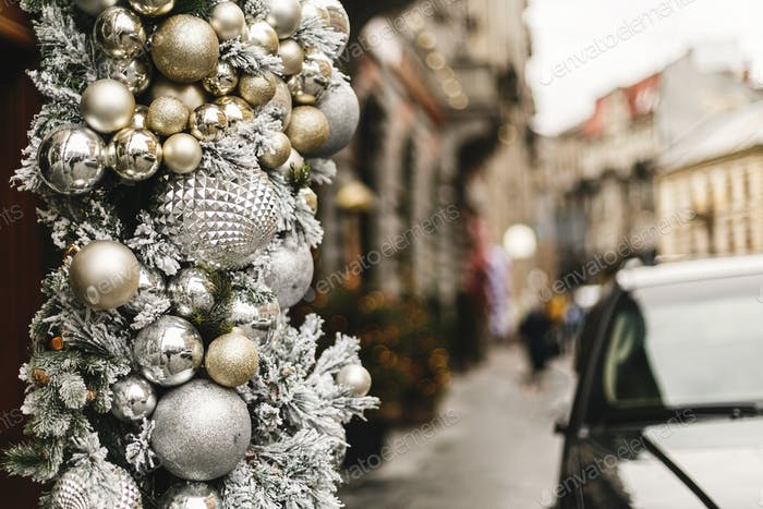Stylish christmas baubles, silver and gold modern ornaments on storefront or building facade