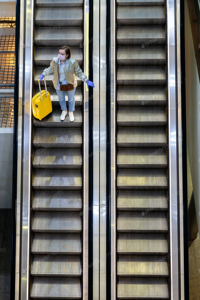 Woman with luggage stands on escalator at airport terminal due to pandemic Covid-19. New normal