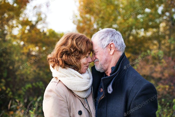 Senior couple in love in an autumn nature, touching noses.