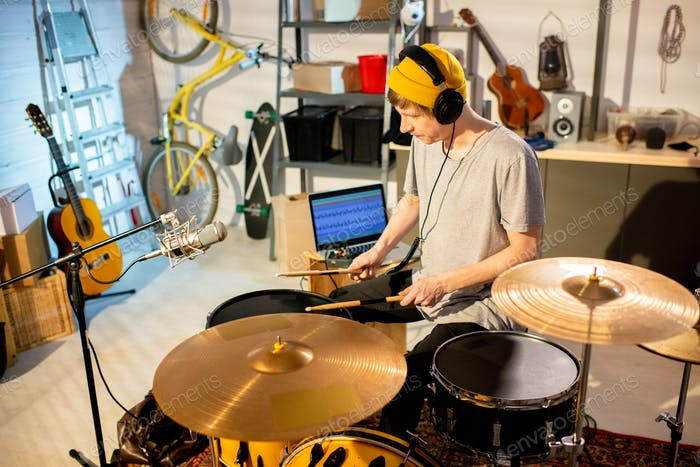 Young musician in t-shirt and beanie hitting drums and cymbals with drumsticks