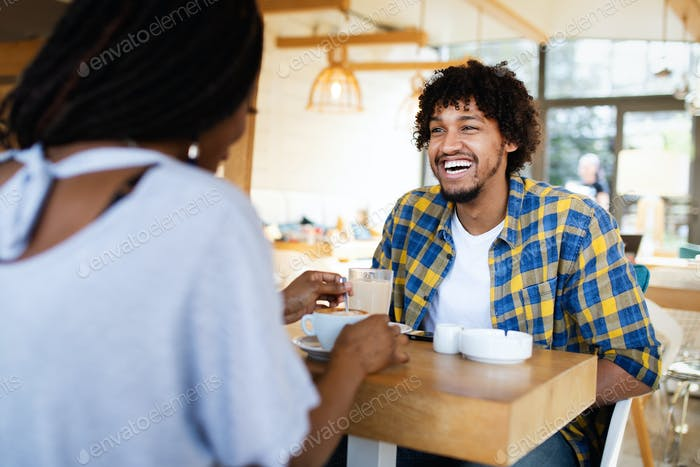 Smiling young african couple sitting at a table at a cafe drinking coffee and talking together