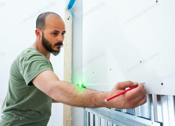 Worker building plasterboard wall.