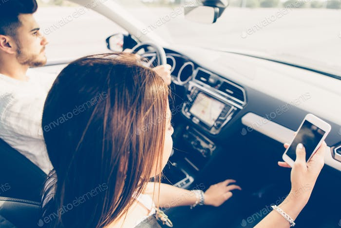 Young woman co-pilot using a mobile phone in a car
