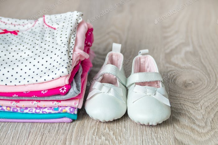 Folded pink and white bodysuit with shoes