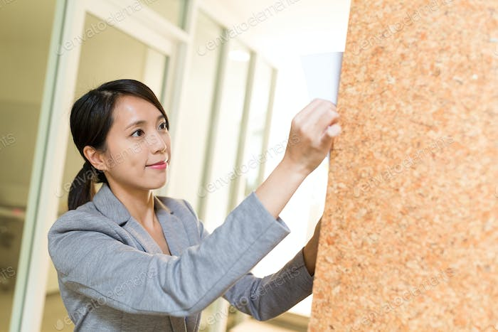 Businesswoman posting paper on the wall inside meeting room