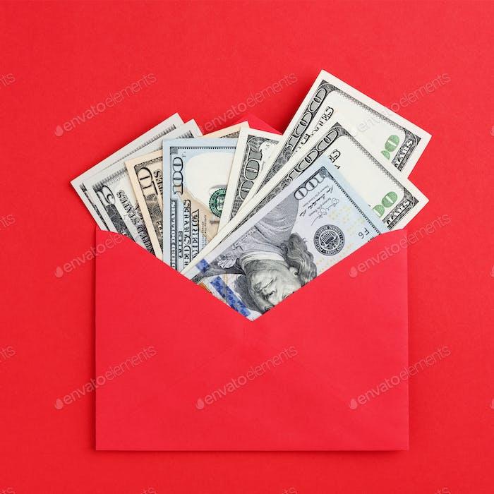 Money Fan US Dollars Inside Envelope on Red Background.