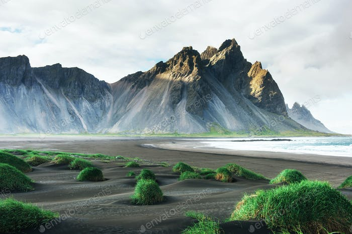 Fantastic west of the mountains and volcanic lava sand dunes on the beach Stokksness, Iceland