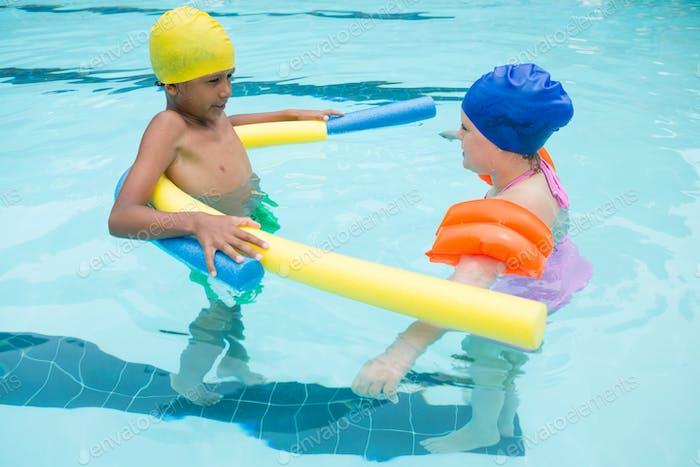 Two kids swimming in pool